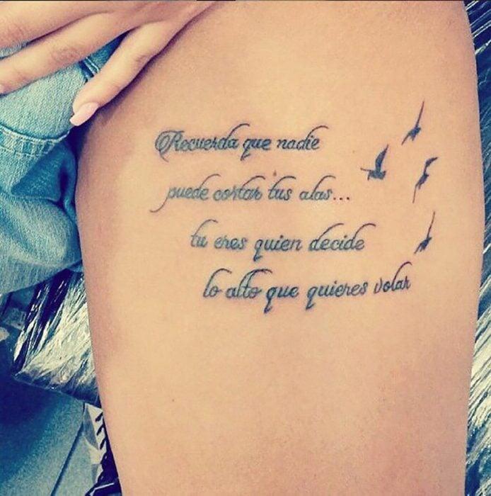 Chica con un tatuaje en el muslo en forma de frase en español