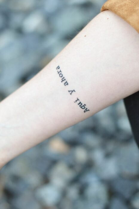 Girl with a tattoo on her wrist in the form of a phrase in Spanish