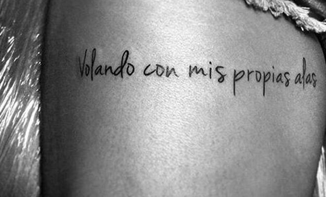 Girl with a tattoo in the form of a phrase in Spanish