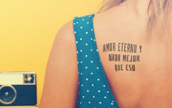 Chica con un tatuaje en la espalda con una leyenda en español