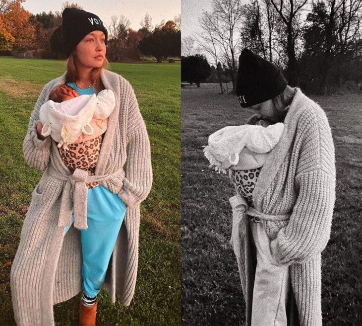 Gigi Hadid cargando a su bebé en brazos en un campo amplio