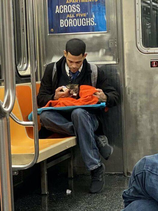 Chico sentado en el metro con saco negro, camisa blanca, corbata negra y jeans con una mochila gris en la espalda, alimenta a gatito café con rayas negras mientras lo arropa con una manta naranja y le da de comer con un biberón