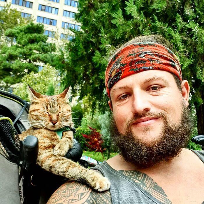 Hombre con barba con camisa de tirantes y paliacate rojo carga una mochila con gato café con rayas negras