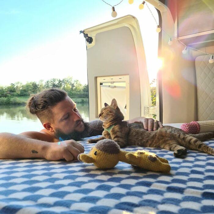 Hombre con barba acaricia a gato en la parte trasera de una furgoneta con tela de cuadros azules y blancos en el piso