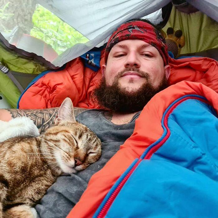 Hombre con barba y chamarra azul con interior negro tomándose selfie en casa de campaña junto a un gato café dormido en su pecho