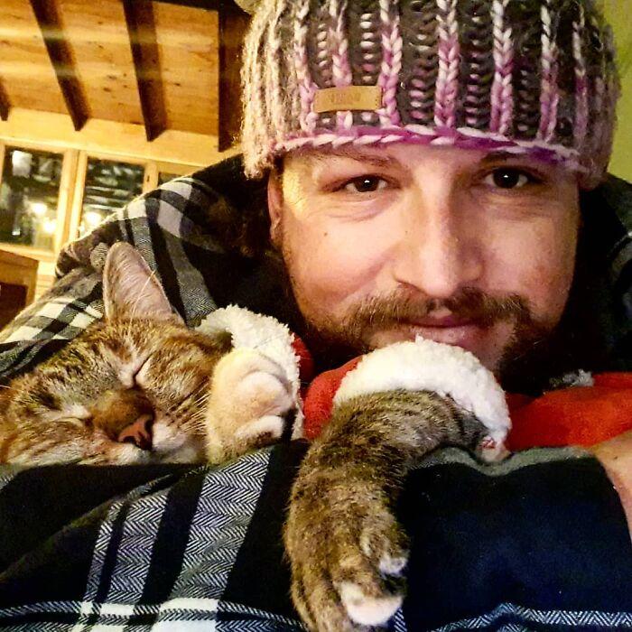 Hombre con barba con gorro tejido abraza a gato dormido con suéter rojo