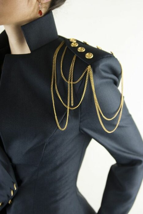 Girl with black jacket and shoulder pad with gold buttons with chains