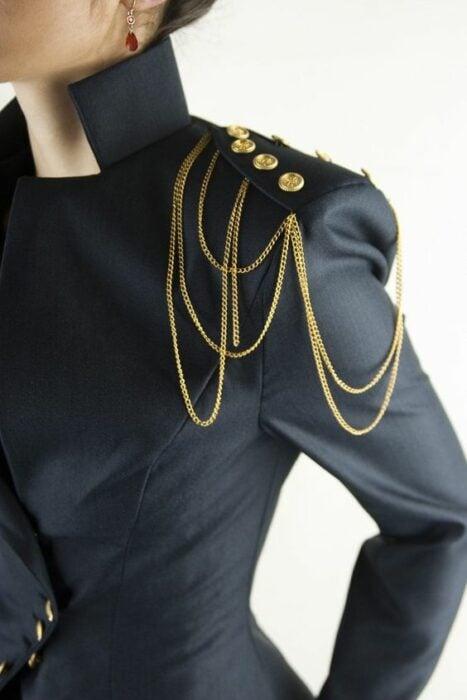 Chica con saco negro y hombrera de botones dorados con cadenasHombreras para decorar tus prendas