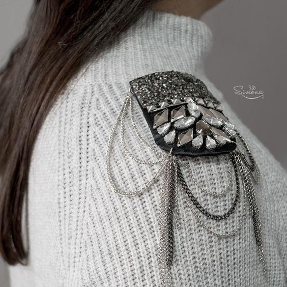 Chica llevando hombreras con pedrería en color gris sobre un suéter a juego; Hombreras para decorar tus prendas