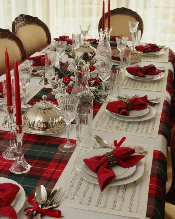 Mesa decorada con cubiertos blancos, moños rojos y manteles a juego; Ideas para decorar la mesa en Navidad
