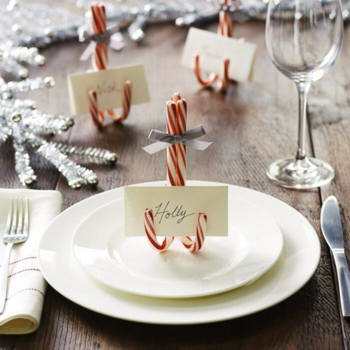 Caramelos de menta sobre una mesa, sosteniendo una tarjeta personalizada; Ideas para decorar la mesa en Navidad