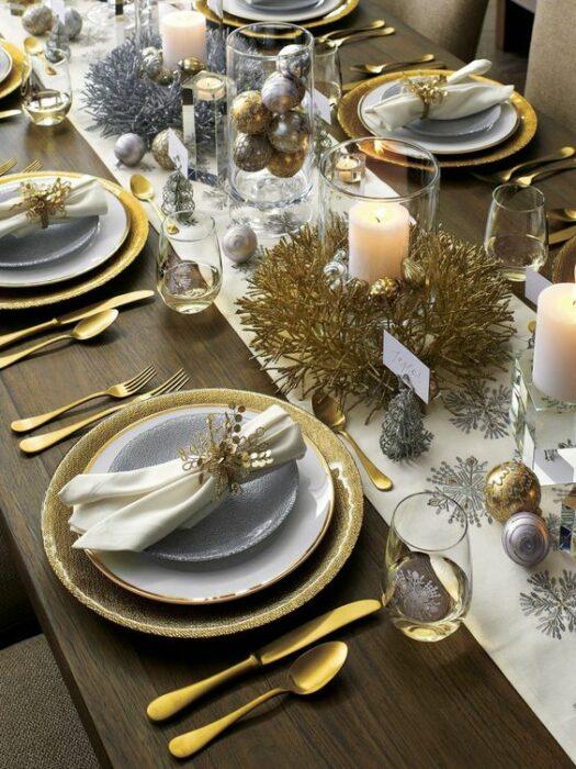 Mesa decorada con cubiertos en tonos blancos y dorados; Ideas para decorar la mesa en Navidad