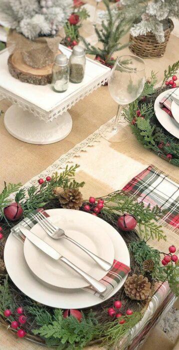 Cubiertos decorados sobre una corona navideña con cascabeles rojos; Ideas para decorar la mesa en Navidad