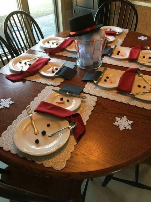 Cubiertos blancos acomodados en forma de muñecos de nieve; Ideas para decorar la mesa en Navidad