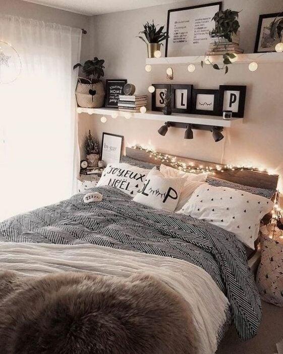 Habitación con paredes blancas con repisas en la pared con cuadros y libros encima y una cama en medio con cobija gris y cojines blancos con puntos negros y serie de luces amarillas para dar luz