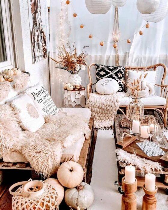 Habitación acogedora en tonos rosas con un sillón blanco cubierto por una tela de peluche blanca decorado con dos cojines y enseguida un sillón de madera con cojín blanco y una manta tejida beige; en el centro hay una mesa con velas y decoración de calabazas