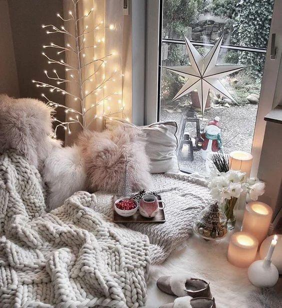 Habitación navideña acogedora con viste al exterior con cama de cobija tejida blanca y cojines de peluche blancos. En medio de la cama una bandeja con dos tazas con chocolate caliente y de lado una mesita blanca con velas y un mini árbol de navidad