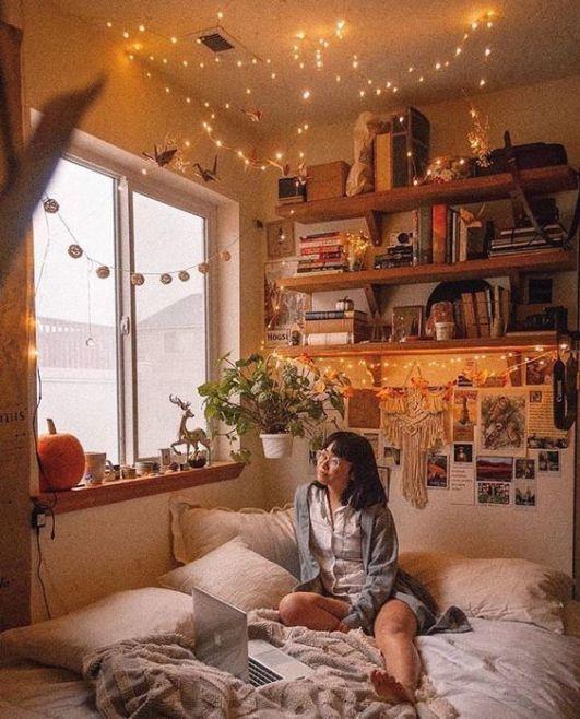 Chica asiática de cabello corto en melena mirando hacia el cielo sentada en una cama de cobijas blancas pegada a la ventana. A espaldas de la chica hay fotos pegadas y arriba unos estantes donde tiene libros y series de luces amarillas