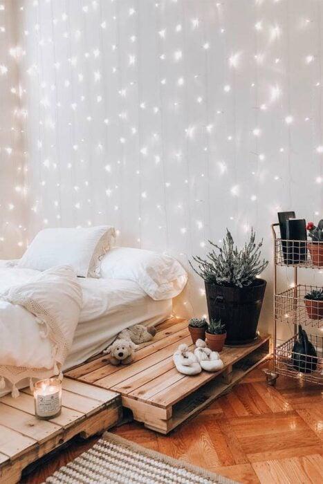 Habitación blanca con una cortina de luces blancas en la pared y una cama en el piso con cobijas blancas y el piso de madera clara. Al lado hay una maceta negra y un organizador de reja color cobre