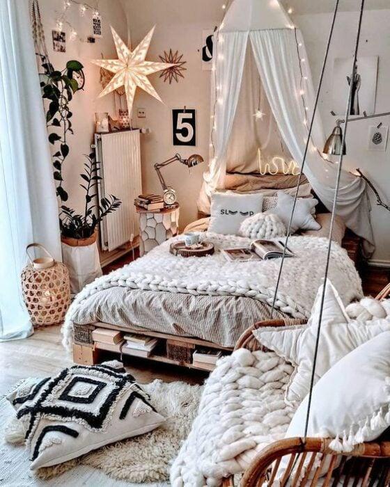 Habitación acogedora con pared blancas, cama con cobijas blancas tejidas y cojines también blancos con una tela arriba de la cama con luces al estilo princesa. En el piso hay una alfombra blanca de peluche