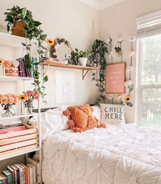 Habitación de mujer con cama y pared blancas. La cama está pegada junto a la venta y se ve el exterior, encima de la cama hay una repisa beige con plantas encima