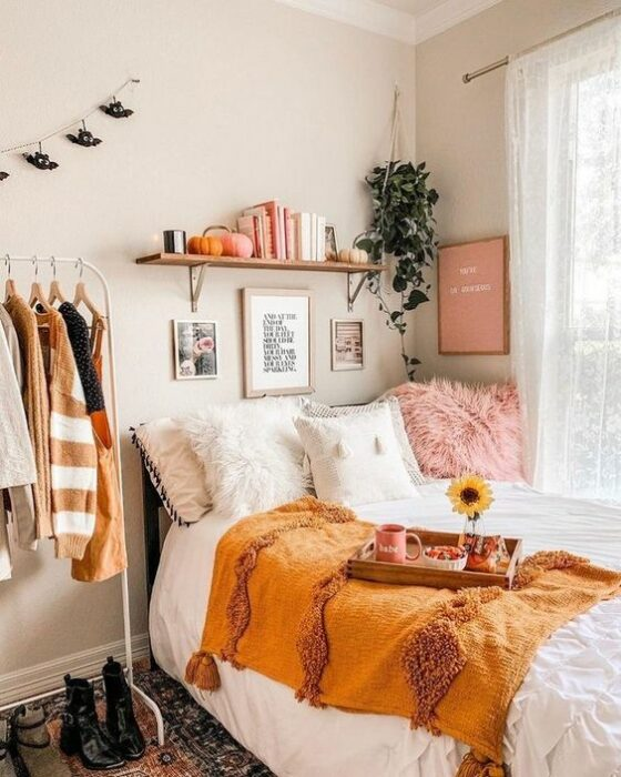 Habitación con paredes blancas, hay una cama pegada a la ventana en una esquina; las cobijas son blancas con un cojín rosa y en medio de la cama hay una frazada naranja en la orilla con una bandeja de comida encima. Al lado de la cama hay un rack de ropa donde hay varios suéteres colgados