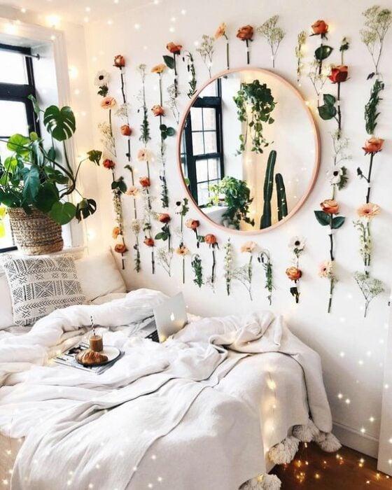 Habitación con paredes blancas y un espejo en medio redondo rodeado de flores naturales pegadas en la pared. Abajo una cama con cobijas blancas pegada la ventana