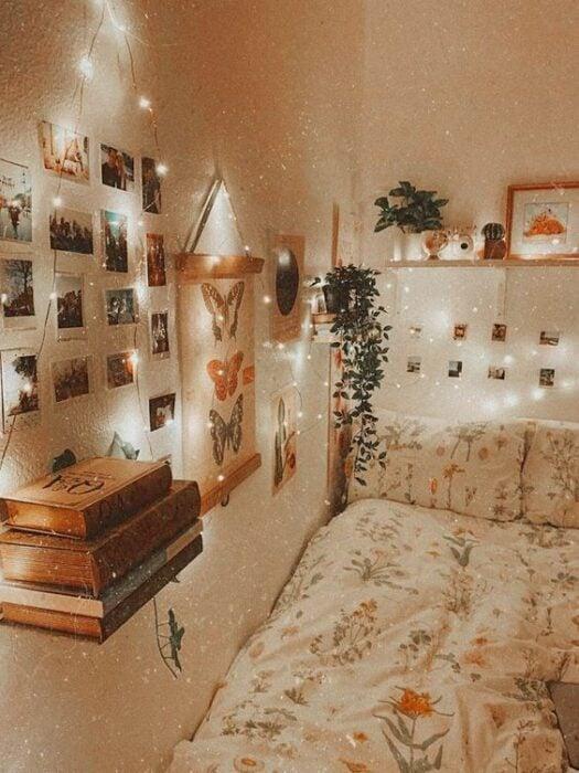 Habitación luminosa de oared blanca con una cama pegada en la esquina del cuarto con cobijas blancas con detalles de flores rosas; en la pared hay fotografías pegadas, un cuadros de mariposas y repisas con flores y una serie de luces amarillas rodeando la cama