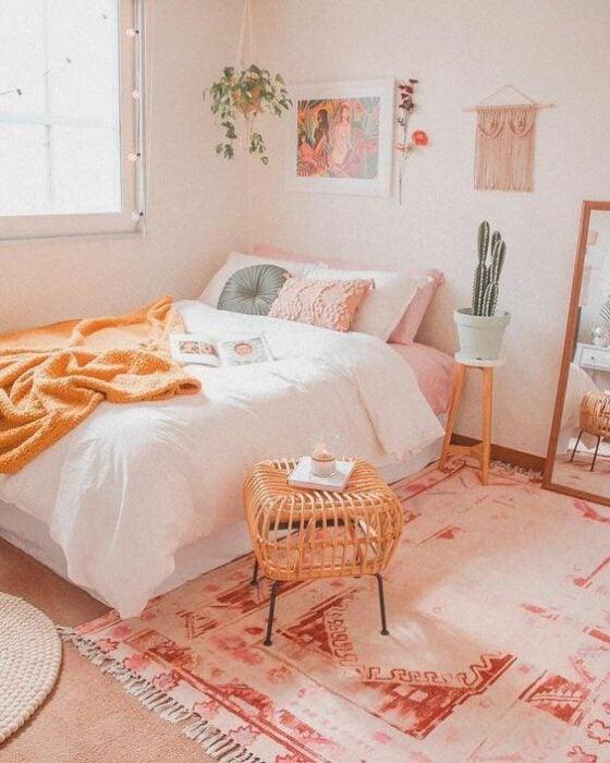 Habitación acogedora para mujer con paredes claras con cuadros y plantas colgando y en la esquina una cama con colcha blanca, cojines rosas y azules, frazada naranja en la orilla y una espejo de cuerpo completo al lado con una alfombra blanca con rosa en el piso