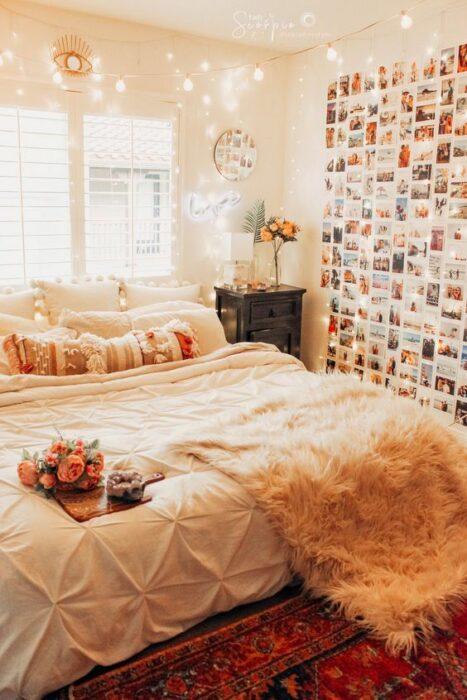 Habitación acogedora con una cama en la parte trasera de la cama con cobijas blancas y una frazada de peluche en la esquina con una bandeja con flores encima. La pared tiene muchas fotos pegadas