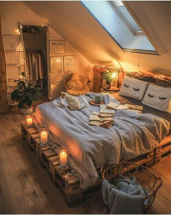 Habitación acogedora con tragaluz abajo de la cama que tiene base de pallets y cobijas grises con cojines blancos y paredes blancas también