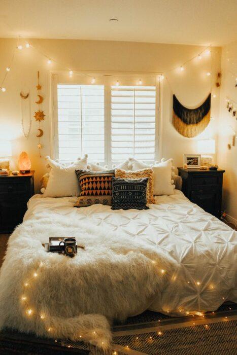 Habitación blanca acogedora con cama de colcha blanca y cojines de cuadros pegada a la ventana con serie de luces en el techo