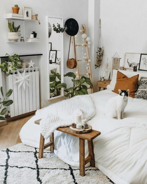 Habitación acogedora con paredes blancas, cama con cobija blanca, cojín café, mesita de  madera para tomar el té, alfombra blanca con rombos de líneas negras y un gato sentado arriba de la cama con cabeza negra y cuerpo blanco