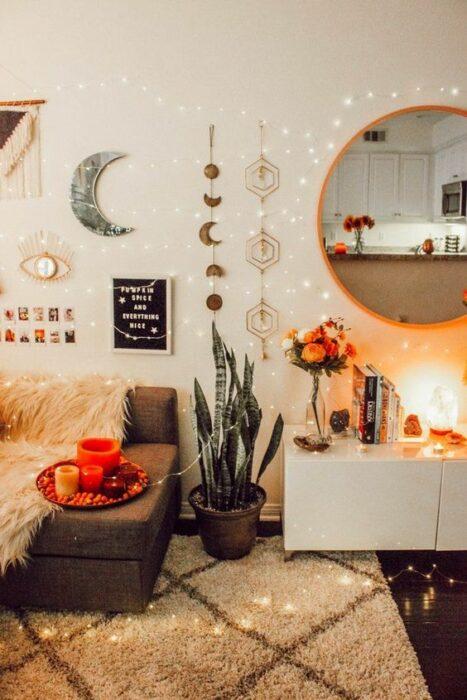 Habitación acogedora de paredes blancas con colgantes de luna, espejo redondo, mueble blanco para poner libros y florero, una planta verde y una sillón café con una tele de peluche blanco encima