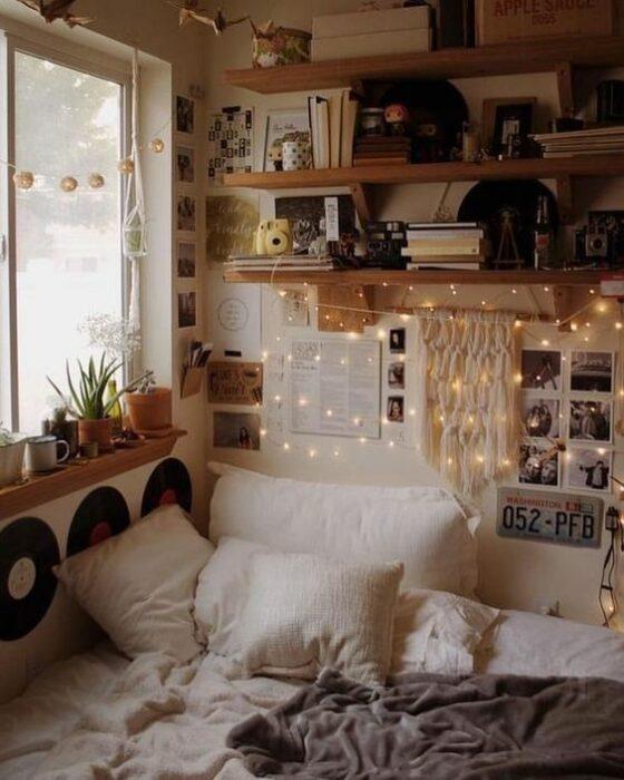 Habitación acogedora con cama en una esquina pegada la ventana con cobijas y cojines blancos y la pared blanca con repisas de madera llenas de discos y libros y series de luces amarillas colgando