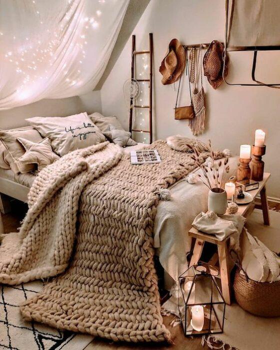 Habitación de noche con luces prendidas muy luminosa con paredes grises y una cama color blanca con una cobija tejida grande color beige y una mesita larga al final de cama con velas