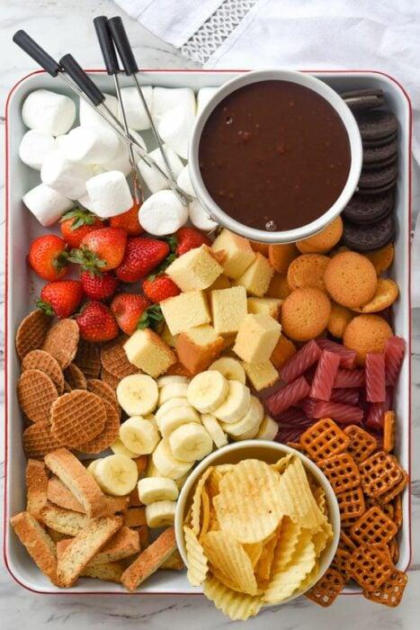 Plato grande con bombones. galletas, plátano y dulces con un recipiente redondo de Nutella
