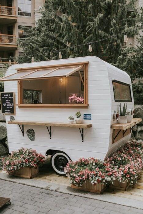 Mini Van de comida en color blanco con detalles cafés rodeada de flores rosas