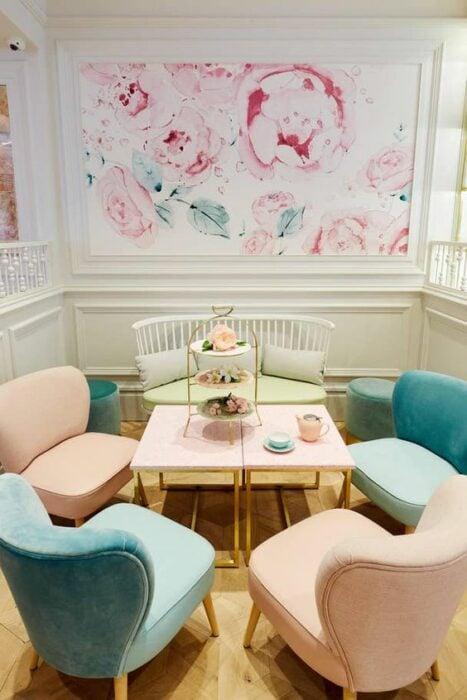 Restaurante con paredes blancas con tapiz de flores rosas con ramas verdes y en el centro de la habitación cinco sillones de colores blancos, azules y rosas con una mesa rectangular rosa en medio