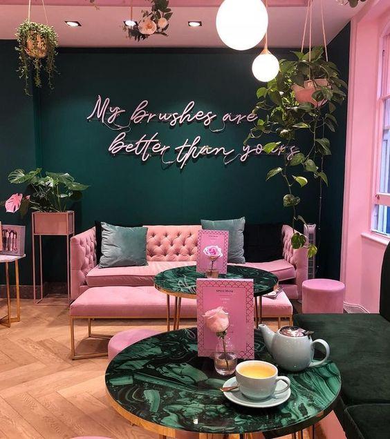 Restaurante con pared de fondo verde esmeralda y las demás rosa con piso de madera y un sillón doble rosa recargado en la pared con cojines verdes de terciopelo