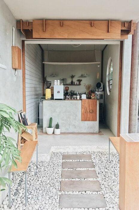 Mini restaurante en material de concreto con mesas y detalles de madera con decoración de plantas y cactus
