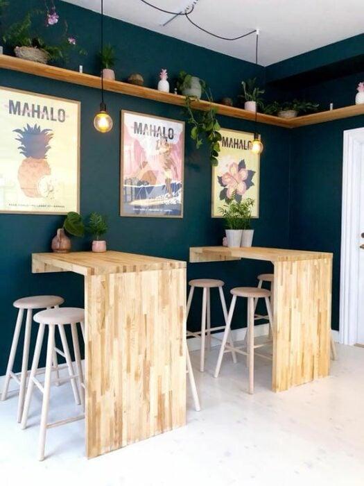 Restaurant con pared verde esmeralda decorado con cuadros tropicales y con mesas de madera pegadas a las pared con bancos altos de asiento redondo