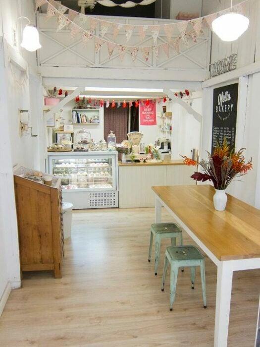 Cafetería en color blanco con mesa rectangular de madera con patas blancas y bancos de metal color menta