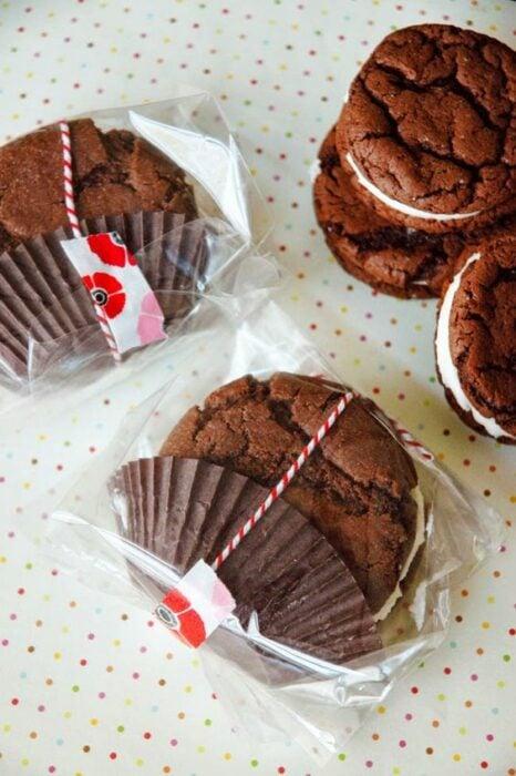 Galletas de chocolate envueltas en bolsitas de celofán transparentes con un lazito rojo con blanco