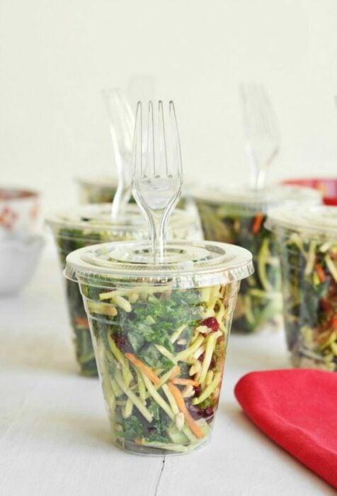 Ensalada para llevar en un vaso transparente con un tenedor