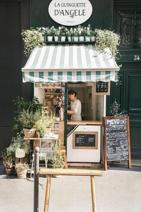 Local pequeño de comida color verde con blanca con plantas afuera y una pizarra