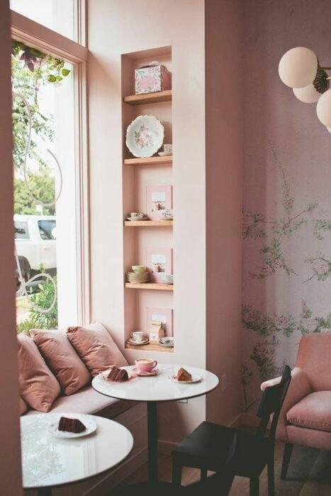 Cafetería color rosa con ventanal grande que da directo a la calle con asiento decorado con tres cojines rosa y una mesa pequeña redonda en medio