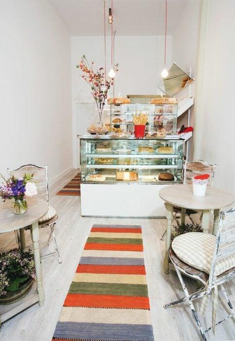 Cafetería blanca con mesa redondas beige con tapete de colores que va directo a la vitrina transparente