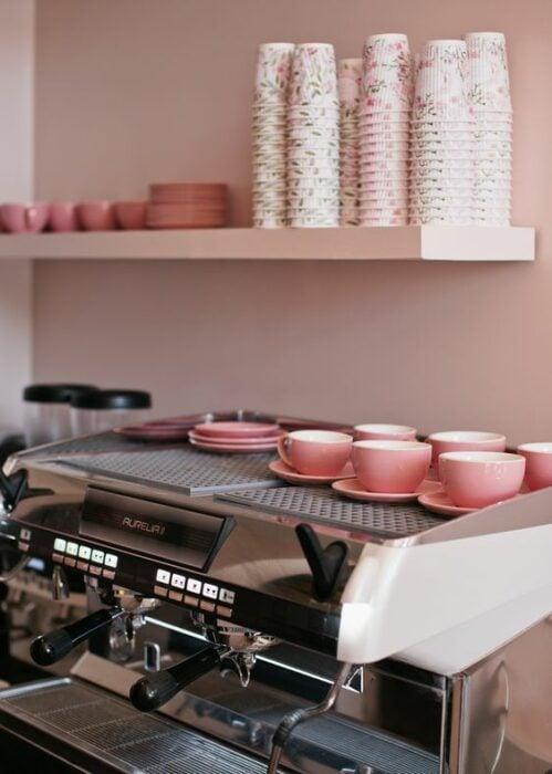 Cafetería de paredes rosas con platos y tazas rosa y maquina de café plateada