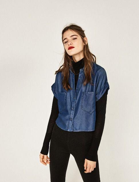 Chica con jeans y camisa de cuello alto negro, combinados con camisa de botones de mezclilla; Ideas para usar camisa de cuello alto